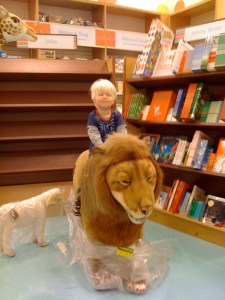E sitting on giant stuffed lion