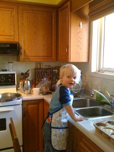 E helping with dishes with his apron on