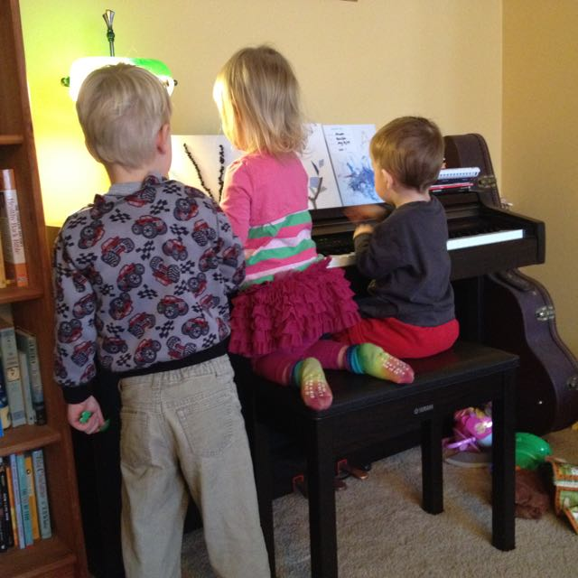 playing piano with three people