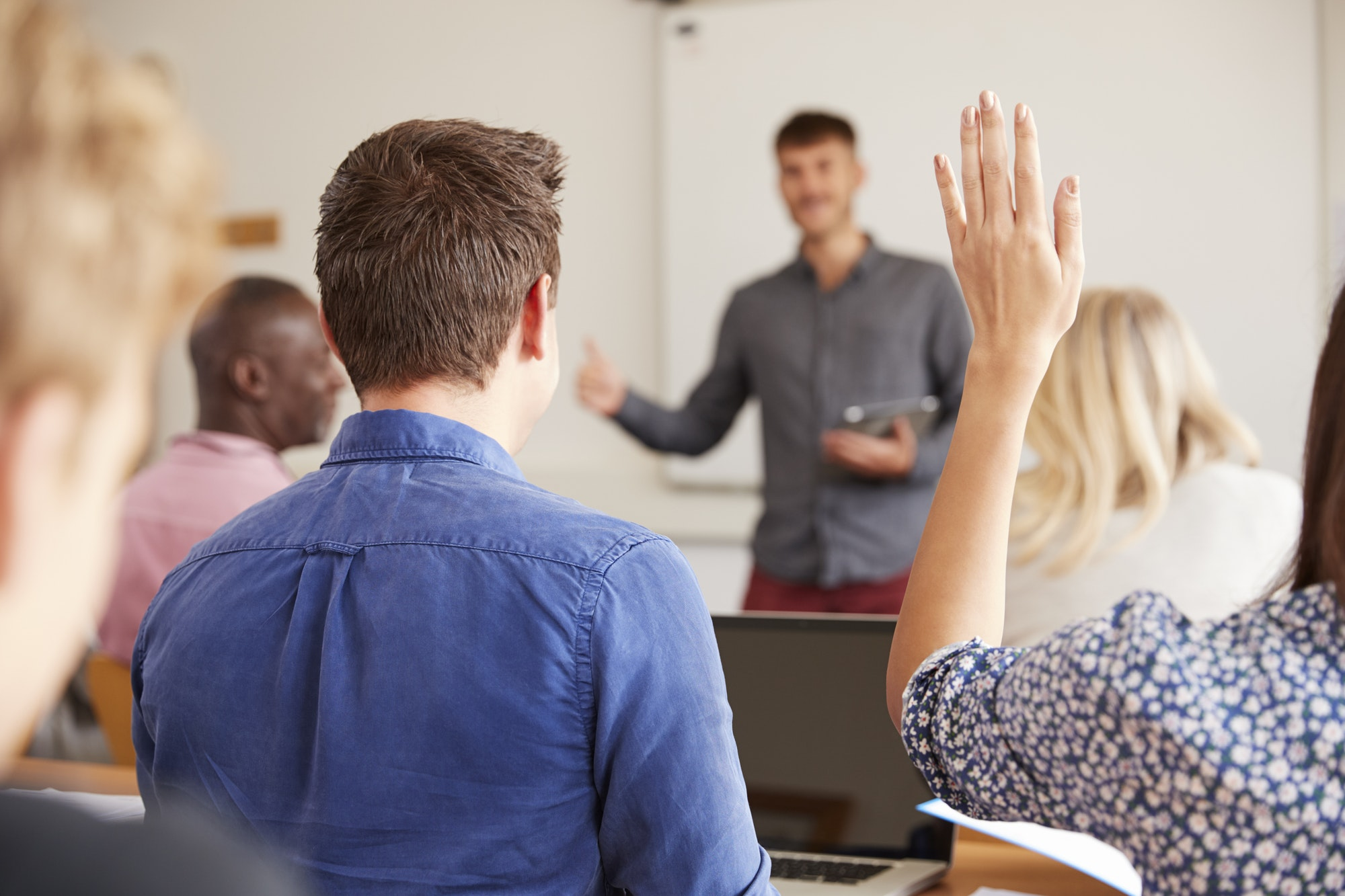 Rear View Of Mature College Student Asking Question In Class