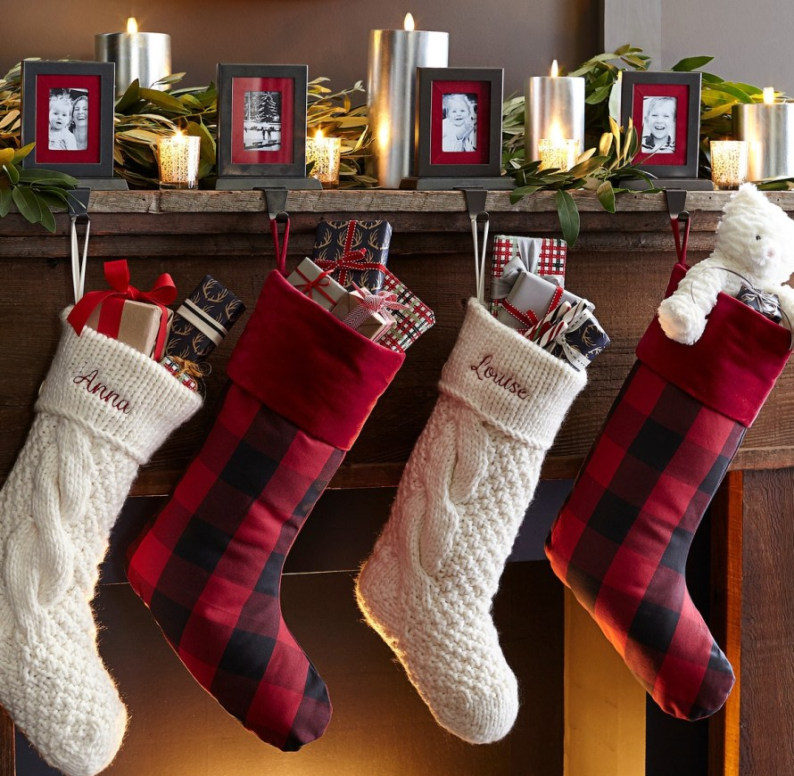 Christmas stockings hanging from picture frame stocking holders at fireplace mantle