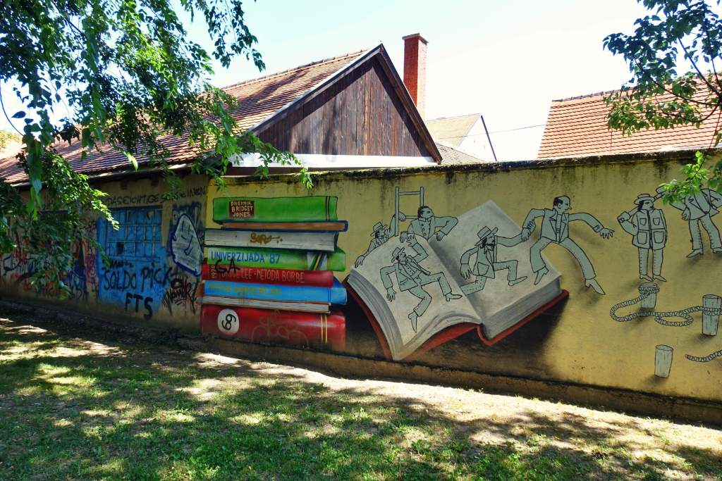 Artwork of people climbing out of a book in Park Opatovina, Zagreb