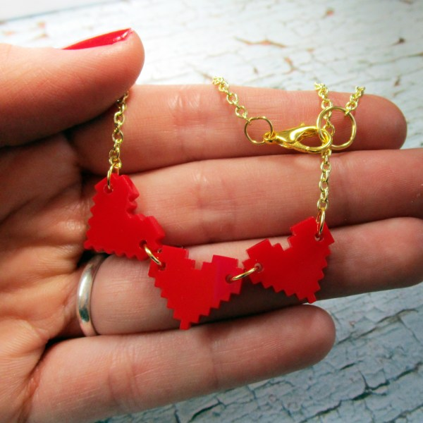 hand holding 3 red pixel hearts gamer girl gold chain necklace
