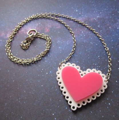 pink heart necklace with chain in curl to show lobster claw clasp on space background