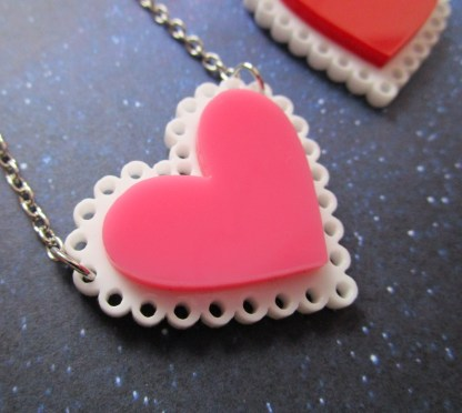 up close view of pink heart on white doily layered acrylic pendant necklace