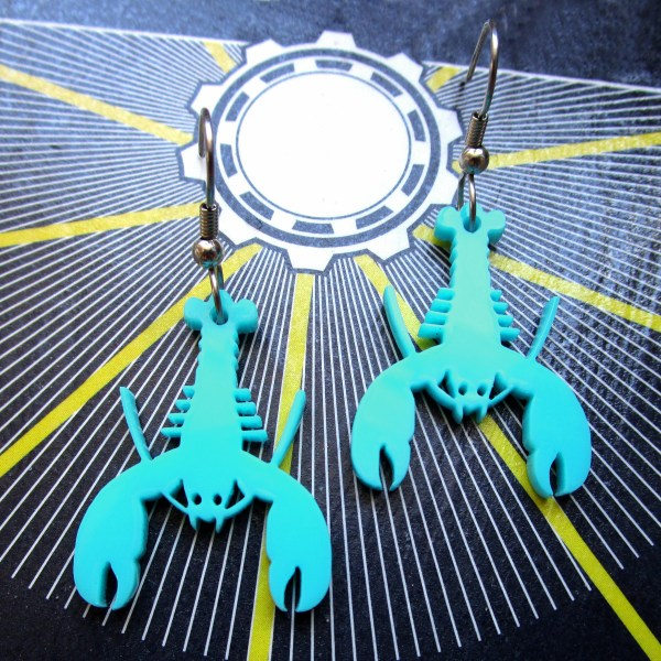 teal lobster earring pendants on black white and yellow background