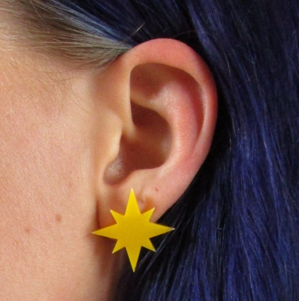 captain marvel earrings on ear to show size