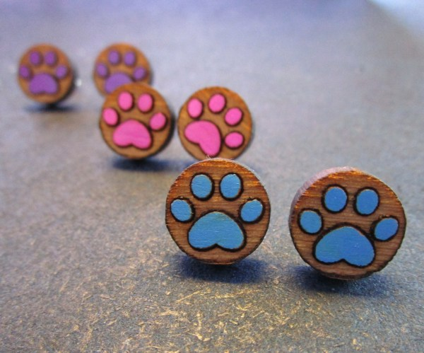 3 pairs of paw print stud earrings in pink purple and blue with space background
