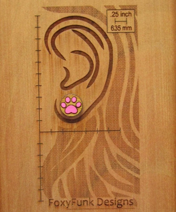pink paw print earring on wooden background with ear and measurements etched into wood