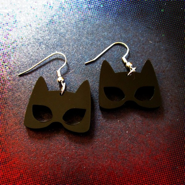 catwoman mask shape earrings on space background