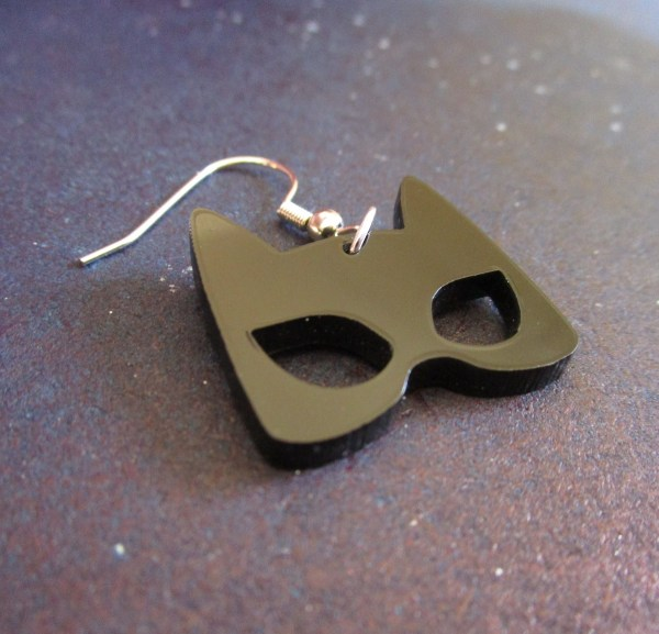 close up of one black cat mask earring to show detail on blue background