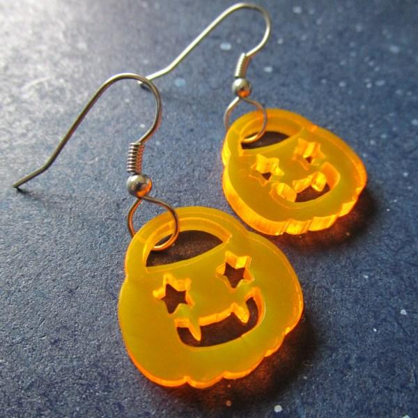 a sideways closeup of 2 neon orange jack o lantern pumpkin pail sheped earring pendants on french earring hooks