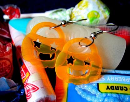 2 neon orange jack o lantern pumpkin pail sheped earring pendants on french earring hooks on top of halloween candy