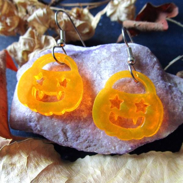 halloween pumpkin pail shaped dangle earring on a rock