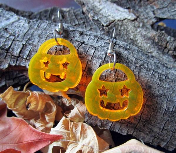 neon orange jackolantern pumpkin dangle earrings on bark background with leaves