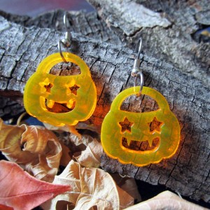 neon orange jackolantern pumpkin dangle earrings on bark background with leaves