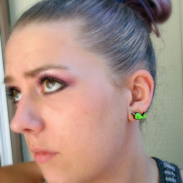 woman face with focus on ear that is wearing a green narwhal stud earring