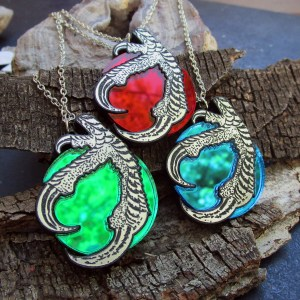 close up of three claw and orb necklaces, one red, one green, one blue necklace pendant on wood bark background
