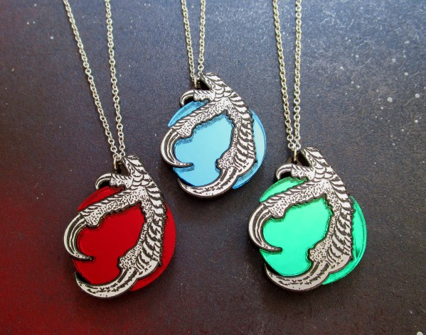close up of three claw and orb necklaces, one red, one green, one blue necklace pendant on space background