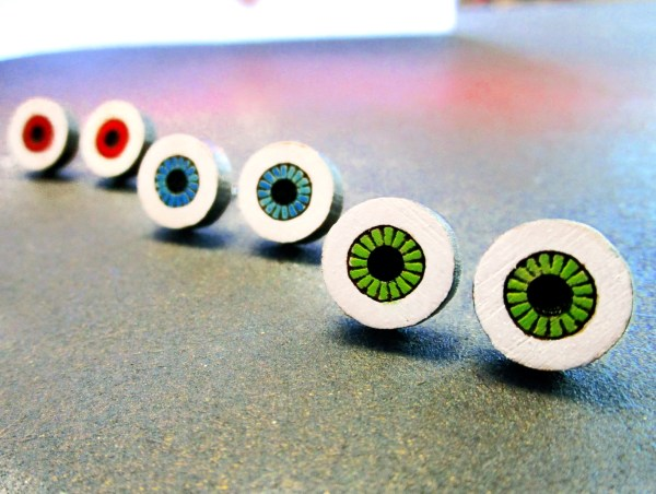 3 sets of wood eye pendant stud earrings, pairs of green, blue and red eye pendants