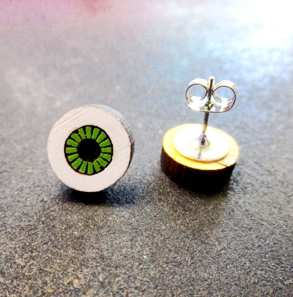 close up of green eyeball earring with earring post pointing up with butterfly clutch