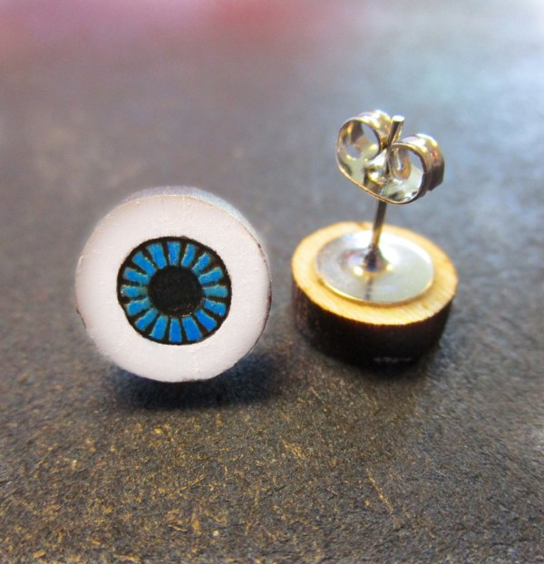 close up of blue eyeball earring with earring post pointing up with butterfly clutch