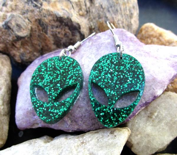 shining green alien dangle earrings on rocks