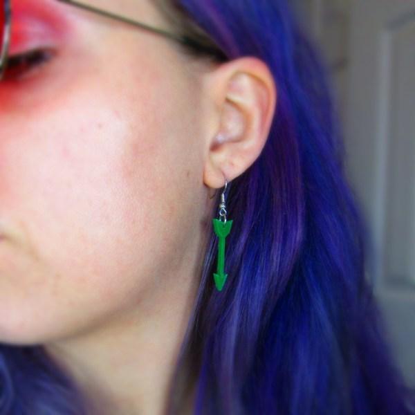 purple hair lady wearing cool green arrow dangle earrings