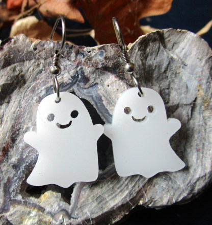 smiling ghost earrings on rock with leaves in background