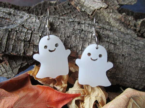 cute ghost dangle earrings hanging on tree bark with fall leaves on bottom