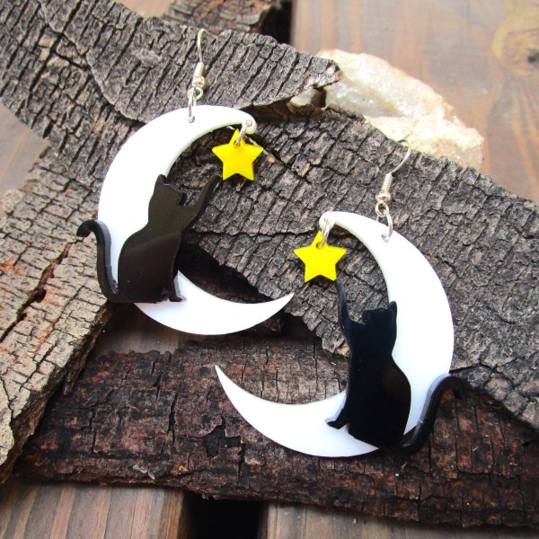 white moon black cat yellow star statement earrings on wood bark background