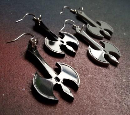 sideways zoom in of battle axe shaped earrings pairs, one pair balck, one pair gray