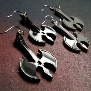 sideways zoom in of battle axe shaped earrings pairs, one pair balck, one pair gray