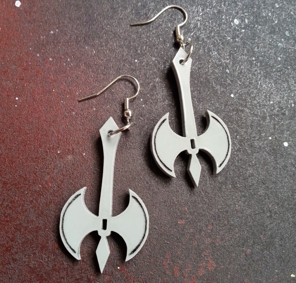 close up of gray medieval battle ax earrings on space background