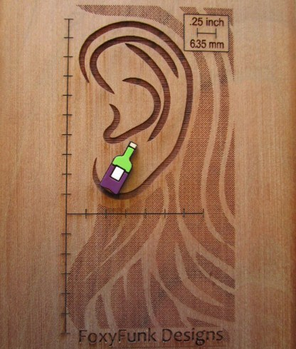 tiny wine bottle stud earring on wood board etched with ear and measurements to show sizw