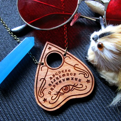 ouiji board planchette necklace with props surrounding pendant