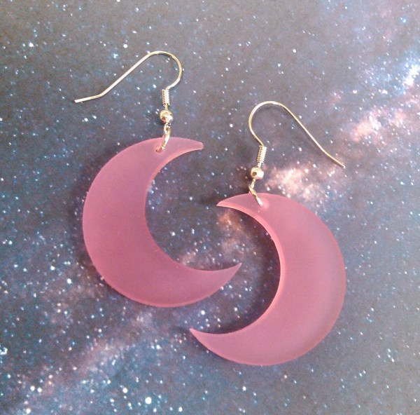 translucent pink crescent moon earrings on space background