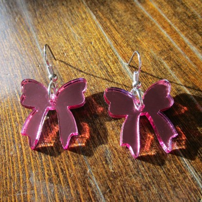 shiny pink ribbon earrings on wooden table