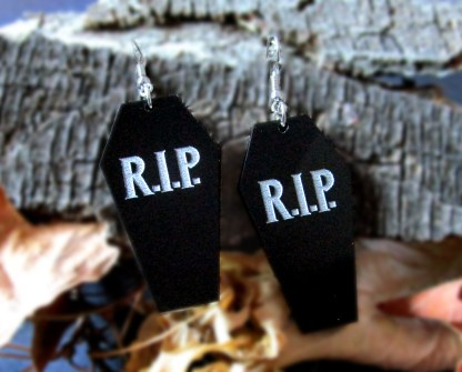 RIP Coffin earrings with natural wood background blurred