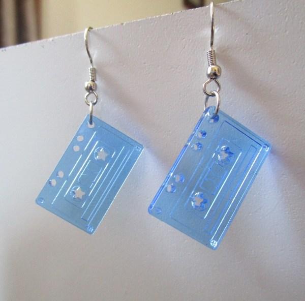 neon blue tape cassette dangle earrings hanging on white board