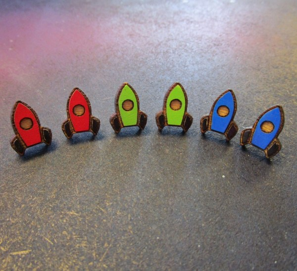 collection of a row of rocket space ship stud earrings of many colors