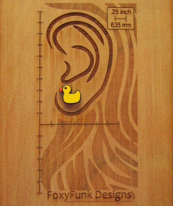 rubber duck earring on wooden board that has been laser engraved with an ear and rulers to show size