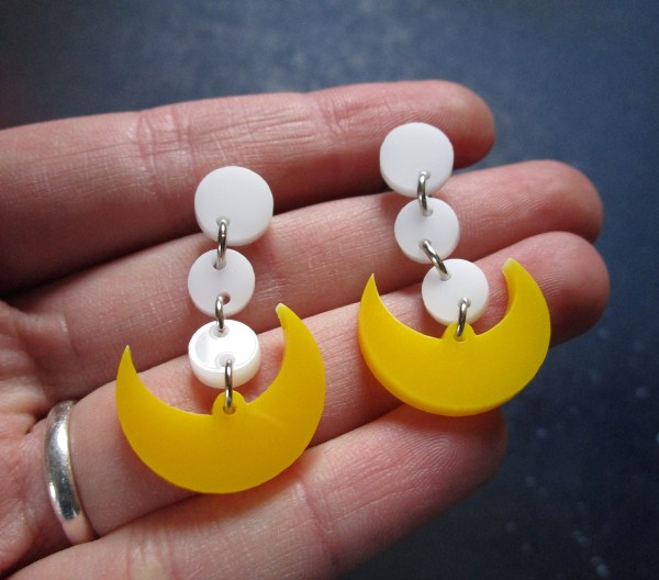 hand holding Sailor Moon Cosplay Earrings to show size