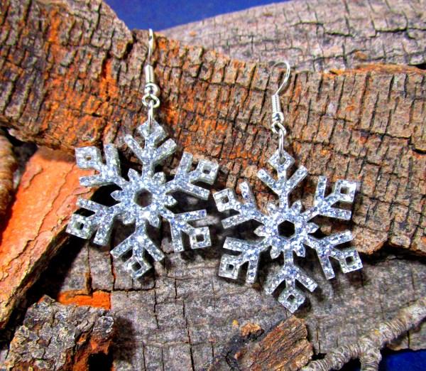 silver glitter snowflake frozen dangle earrings on wood background