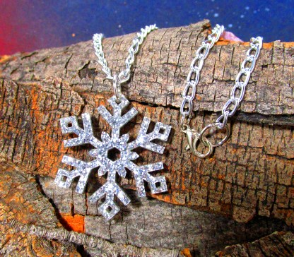 silver glitter snowflake pendant necklace on wood background
