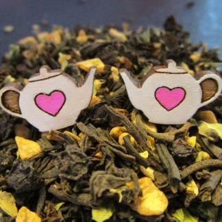 Tiny Heart Teapot Earrings sitting upon loose tea leaves