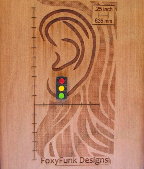 Tiny Traffic Stop Light Earring on wooden background with ear laser etched out to show size