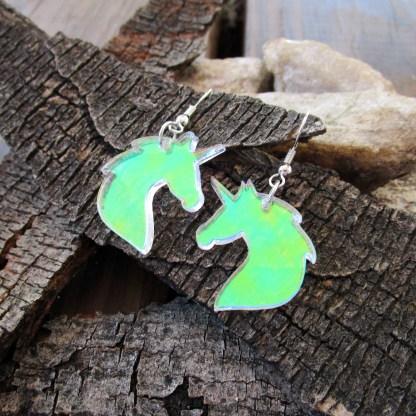 Shining iridescent unicorn bust shaped dangle earrings on wood bark