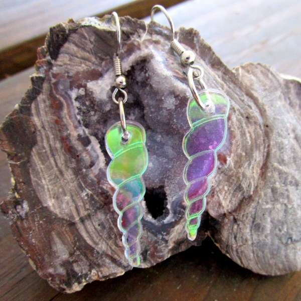 set of unicorn horn earrings showing rainbow colors hanging on rock