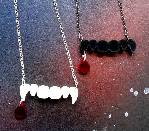vampire pendant halloween necklace one black, one white on space background